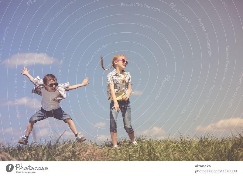 Bruder und Schwester spielen tagsüber auf dem Spielfeld. Kinder haben Spaß im Freien. Sie laufen auf dem Rasen. Konzept der freundlichen Familie. Lifestyle