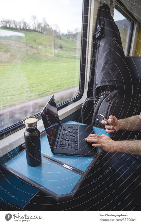Mann benutzt Laptop und Telefon im Zug. Schweizer Zuginnenraum Ferien & Urlaub & Reisen Tourismus Ausflug Stuhl Tisch Arbeit & Erwerbstätigkeit Verkehr