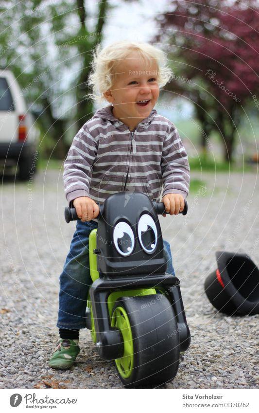 Lachender Junge auf Laufrad Freizeit & Hobby Sommer Fahrradfahren Kindererziehung Mensch maskulin Kleinkind Kindheit 1 1-3 Jahre Frühling Park Hut blond Locken
