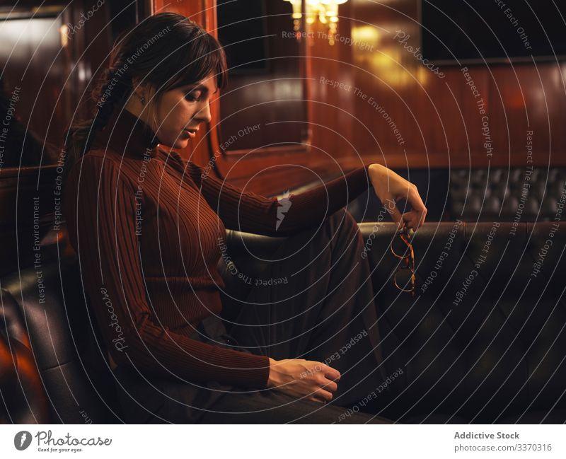Stilvolle Frau auf Ledersofa sitzend stylisch elegant Mode Liege bequem Model schwarz Dame trendy schick traumhaft modisch Pullover Möbel nachdenklich Glamour