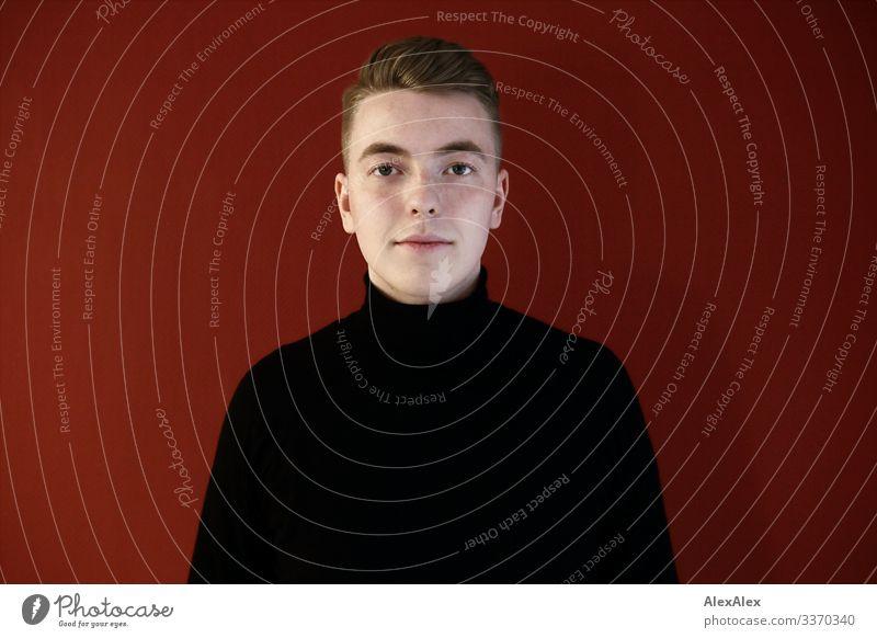 Portrait eines jungen Mannes vor roter Wand Lifestyle Stil schön Wohlgefühl Wohnung Junger Mann Jugendliche Gesicht 18-30 Jahre Erwachsene Pullover blond