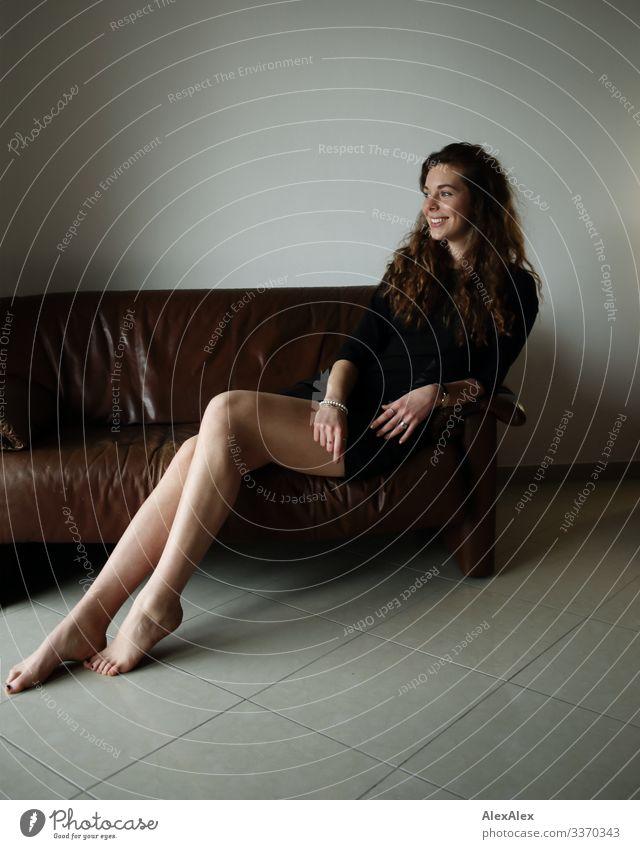 Portrait einer jungen, großen Frau, die barfuß auf einer braunen Leder- Couch sitzt und lächelt Stil Freude schön Wohlgefühl Wohnung Sofa Junge Frau Jugendliche