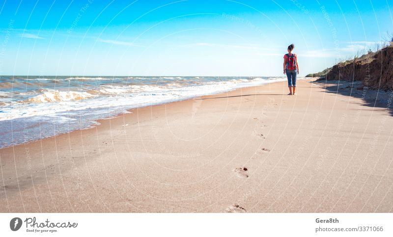 eine Touristin mit rotem Rucksack an einem leeren Sandstrand Ferien & Urlaub & Reisen Freiheit Sommer Strand Meer Wellen Frau Erwachsene Natur Landschaft Himmel