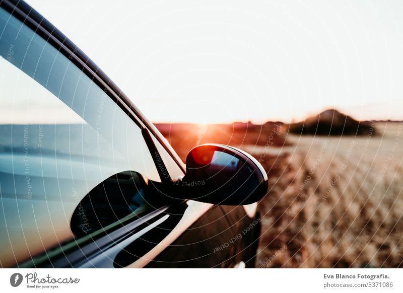 Nahaufnahme eines Autos und eines Rückspiegels bei Sonnenuntergang auf einem Feld. Reisekonzept PKW reisen sonnig Landschaft gelb niemand Ansicht sportlich