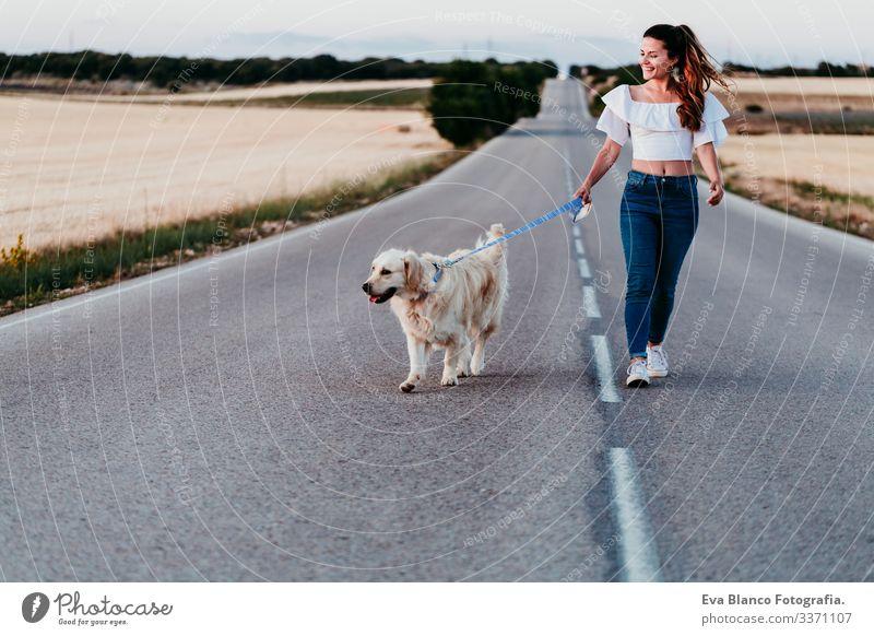eine junge Frau, die bei Sonnenuntergang mit ihrem Golden Retriever-Hund an der Straße spazieren geht. Haustiere im Freien urban Landschaft Feld laufen Glück