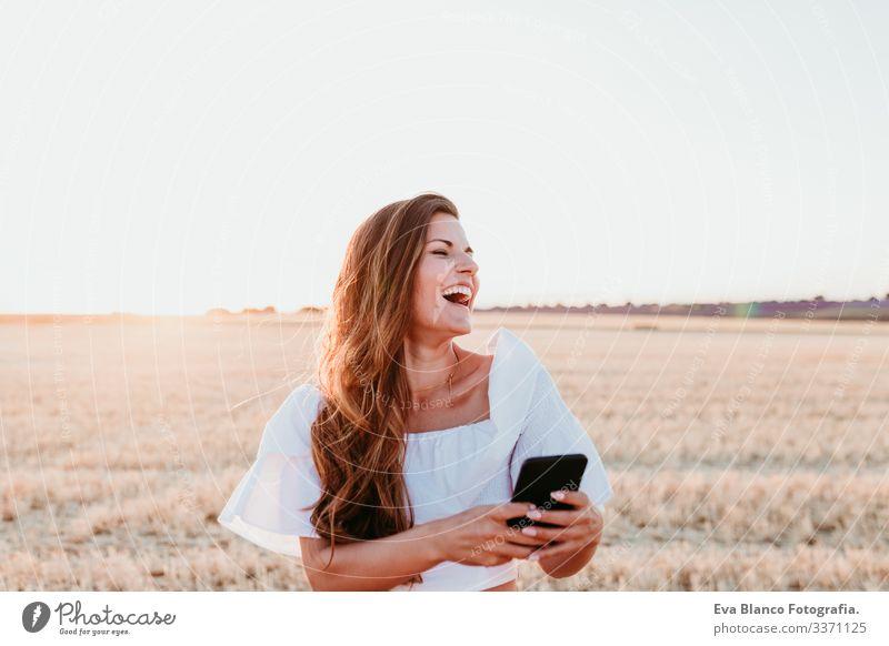 junge schöne frau auf dem land bei sonnenuntergang mit dem handy. technologiekonzept Handy Technik & Technologie Porträt Frau Sonnenuntergang im Freien