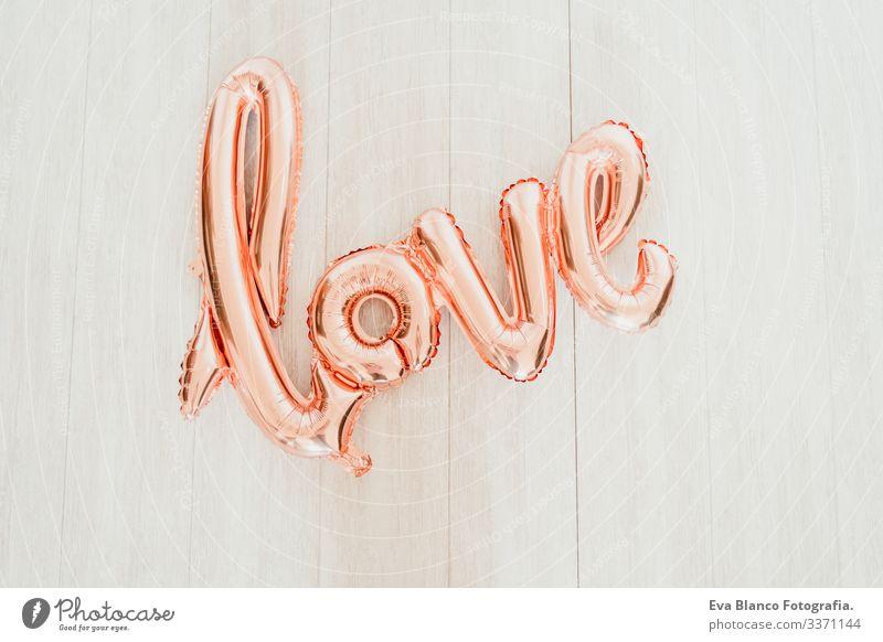 Draufsicht auf den rosa LOVE-Ballon. Valentines-Konzept Liebe Luftballon Form Wort heimwärts im Innenbereich Atelier vereinzelt niemand Folie Pastell