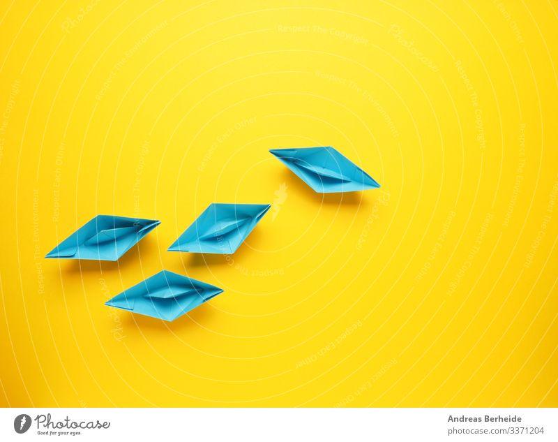 Teamwork-Geschäftskonzept mit Papierboot auf gelbem Hintergrund Weg Idee beeinflussen Lösung Kreativität Innovation innovativ Kompass inspirieren einzigartig