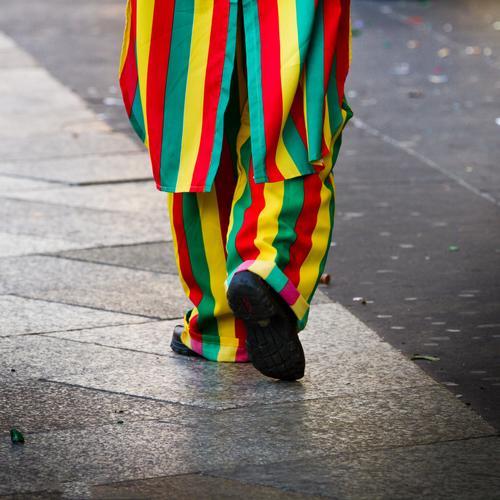Ein Jeck Karneval maskulin feminin 1 Mensch Fußgänger Bürgersteig Karnevalskostüm Linie Streifen Feste & Feiern gehen authentisch Fröhlichkeit lustig positiv