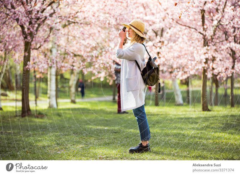 Porträt einer schönen Frau mit Strohhut, die in einem schönen Park mit blühenden Kirschbäumen reist und Fotos mit einer Retro-Kamera macht. Tourist mit Rucksack.