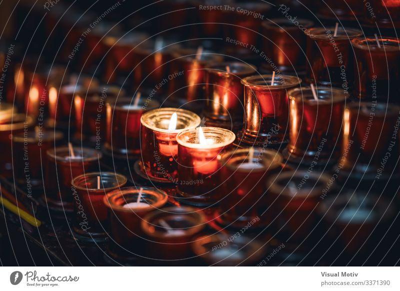 Zwei brennende Kerzen zwischen mehreren Reihen von roten Kerzen in einer Kirche Erholung Meditation Wärme hell Hoffnung Farbe Frieden Glaube Religion & Glaube