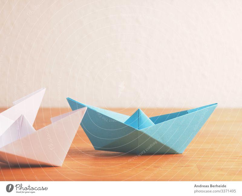Teamwork-Geschäftskonzept mit Papierboot auf einem Holztisch Hintergrund blau Boot Business Farbe Kompass Konkurrenz Konzept Textfreiraum kreativ Kreativität