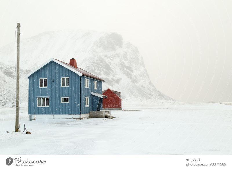 Blaues Haus im Schnee vor verschneitem Berg Norwegen Winter Lofoten Skandinavien Winterlandschaft Schneien Strom Strom Mast Stromversorgung Klima Klimawandel