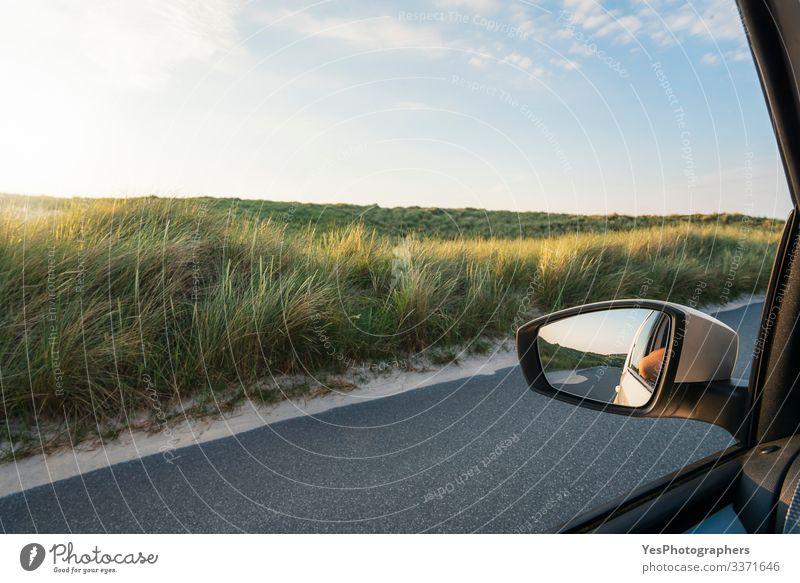 Autofensteransicht mit Grasdünen und Straße auf der Insel Sylt Ferien & Urlaub & Reisen Tourismus Ausflug Sommer Spiegel Landschaft fahren Perspektive