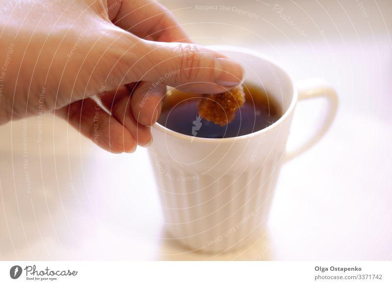 In eine weiße Tasse legt die Hand der Frau ein Stück braunen Zucker Tisch Bonbon Nahaufnahme heiß Getränk Kaffee Café Frühstück natürlich Dessert lecker