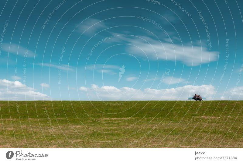 Pärchen Arm in Arm auf Parkbank mit grüner Wiese und blauem Himmel Wolken Schönes Wetter alt ruhig Fernweh Horizont Idylle Farbfoto Außenaufnahme Tag Weitwinkel