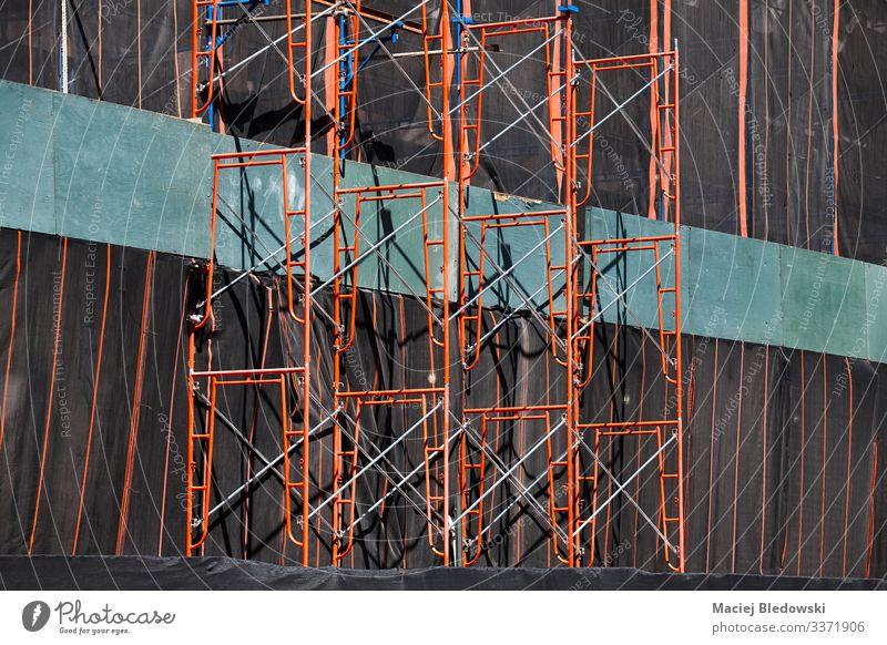 Gerüstsystem an einem zu renovierenden Gebäude. Industrie Baustelle Mauer Wand Fassade Metall rot Sicherheit Schutz Verlässlichkeit Konstruktion industriell