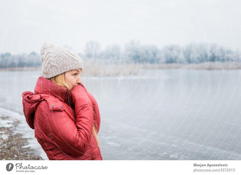 Junge Frau steht im Winter am zugefrorenen See Lifestyle Abenteuer wandern feminin Jugendliche Erwachsene 1 Mensch 30-45 Jahre Umwelt Natur Landschaft Wasser