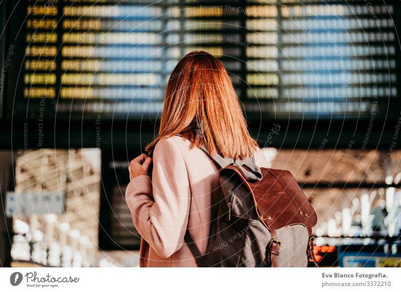junge Frau am Bahnhof, die auf die Zieltafel schaut. Konzept für Reisen und öffentliche Verkehrsmittel Bildschirm Ausflugsziel reisen Rucksack Rückansicht