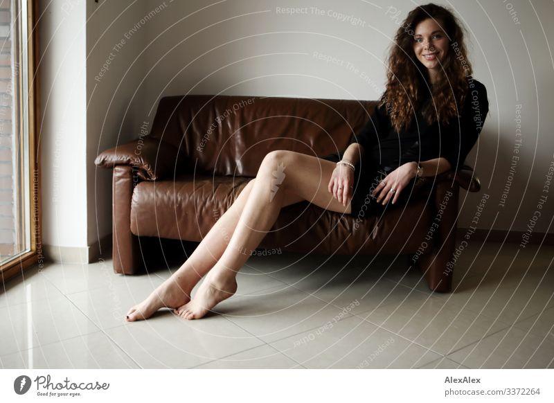 Portrait einer jungen, großen Frau, die barfuß auf einer braunen Leder- Couch sitzt und lächelt Stil Freude schön Leben Wohlgefühl Wohnung Sofa Junge Frau