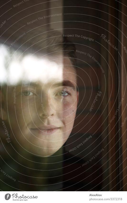 Portrait eines jungen Mannes hinter der Fensterscheibe mit Reflexionen Stil schön Zufriedenheit Wohnung Raum Junger Mann Jugendliche Gesicht 18-30 Jahre