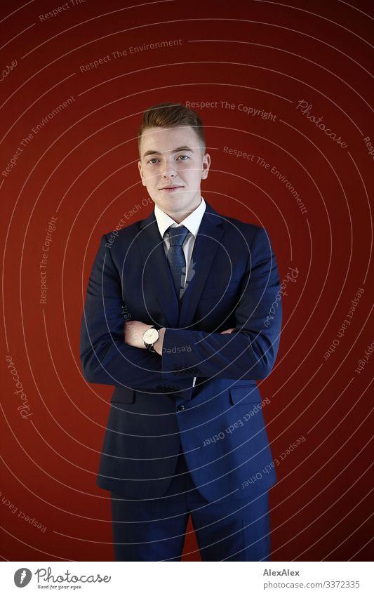 Junger Mann im Anzug vor roter Wand Lifestyle Reichtum Stil Freude schön Wohlgefühl Büro Werkstatt Jugendliche 18-30 Jahre Erwachsene Krawatte blond kurzhaarig