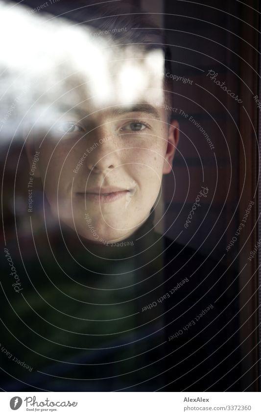 Portrait eines jungen Mannes hinter Fensterscheibe elegant Stil schön Wohlgefühl Wohnung Junger Mann Jugendliche Gesicht 18-30 Jahre Erwachsene Schönes Wetter