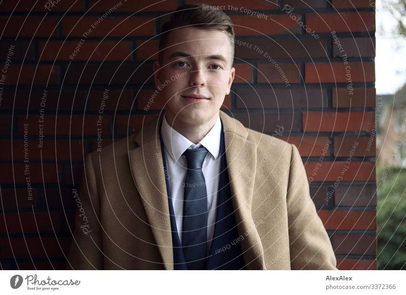 Portrait eines jungen Mannes Lifestyle Stil Freude schön Leben Backsteinwand Balkon Junger Mann Jugendliche 18-30 Jahre Erwachsene Schönes Wetter Anzug Mantel