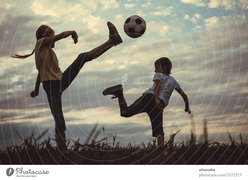 Fröhliche kleine Jungen und Mädchen spielen auf dem Spielfeld mit Fussball. Kinder, die im Freien Spaß haben. Konzept des Sports. Lifestyle Freude Glück