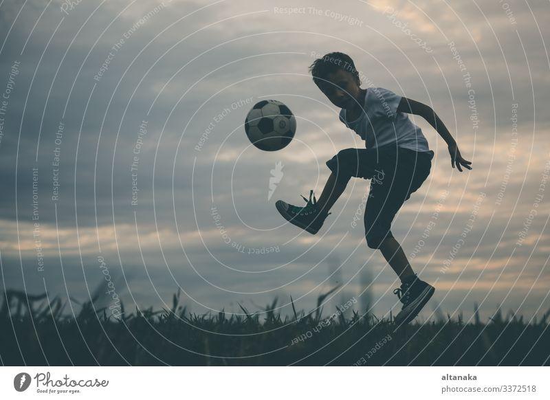 Kleiner Junge spielt auf dem Feld mit dem Fußball. Lifestyle Freude Glück Erholung Freizeit & Hobby Spielen Sommer Sport Kind Mensch Mann Erwachsene Kindheit