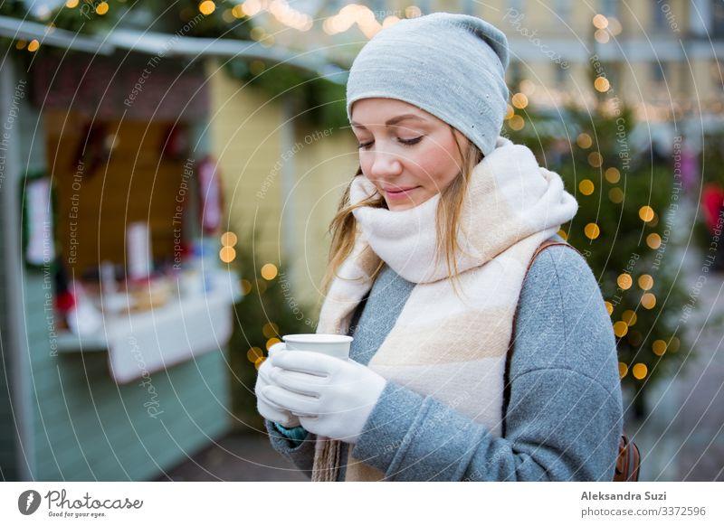 Junge Frau auf dem Weihnachtsmarkt trinkt eine Tasse heiße Schokolade mit Marshmallow und trägt eine warme Strickmütze und einen Schal. Beleuchtete und dekorierte Kioske und Geschäfte im Hintergrund. Helsinki, Finnland