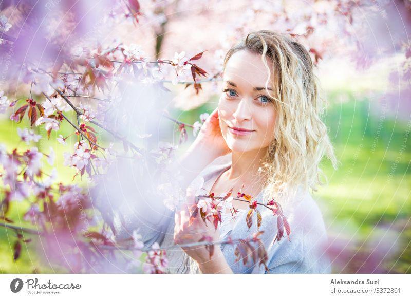 Junge Frau genießt die Natur im Frühling. Atmen frische Luft und Blumen Aroma in schönen Park mit Kirschbäumen in der Blüte. Glück Konzept Beautyfotografie