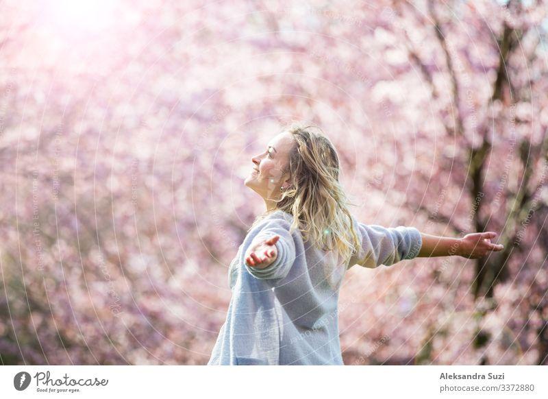 Junge Frau genießt die Natur im Frühling. Tanzen, laufen und wirbeln in schönen Park mit Kirschbäumen in der Blüte. Glück Konzept Beautyfotografie Körperpflege