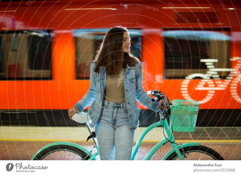 Teenager in Jeans mit gelbem Rucksack und Fahrrad in der U-Bahn-Station stehend, auf den Zug wartend, lächelnd, lachend. Oranger Zug fährt hinter dem Mädchen vorbei. Futuristischer U-Bahnhof. Finnland, Espoo
