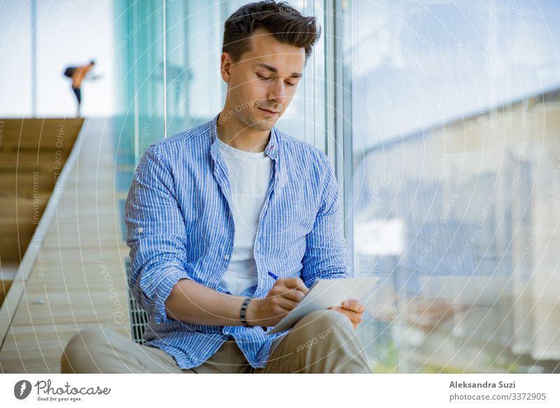 Mann schreibt in einem Notizbuch, sitzt auf Stufen an großen Fenstern, großer Arbeitsraum. Erwachsener Buch lässig Checkliste konzentriert Konzept kreativ