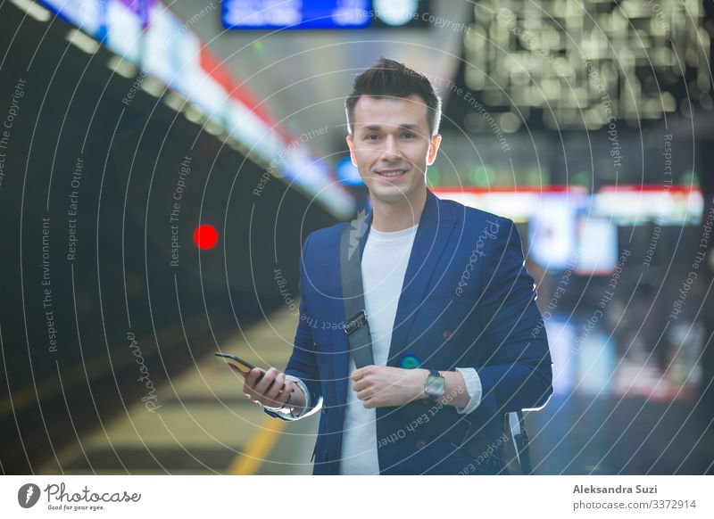 Junger, stilvoller, gut aussehender Mann im Anzug mit Koffer steht auf der Metrostation, hält ein Smartphone in der Hand, scrollt und simst, lächelt und lacht.
