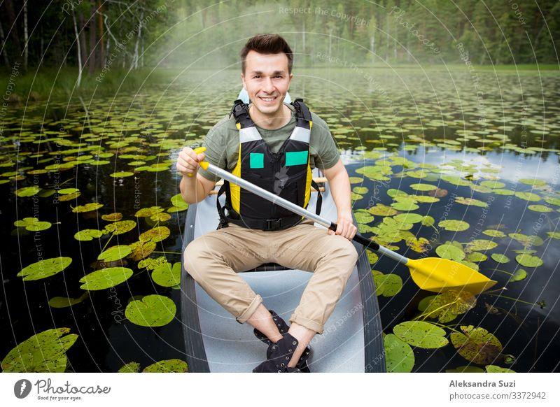 Zwei Männer in Rettungswesten beim Kanufahren auf einem Waldsee. Aktion gehen Abenteuer offen Ausflugsziel entdecken Finnland Glück See Landschaft Lifestyle
