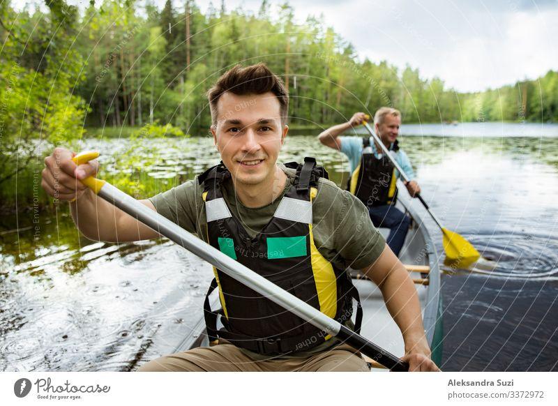 Zwei Männer in Rettungswesten beim Kanufahren auf einem Waldsee. Aktion Abenteuer offen Ausflugsziel entdecken Finnland Glück See Landschaft Lifestyle Mann