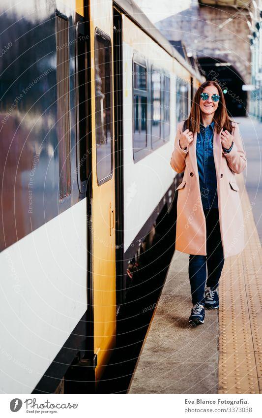 eine glückliche junge Frau, die am Bahnhof spazieren geht. Reisekonzept Bildschirm Ausflugsziel reisen Rucksack Kaukasier Europa Eisenbahn Warten Wagen Schiene