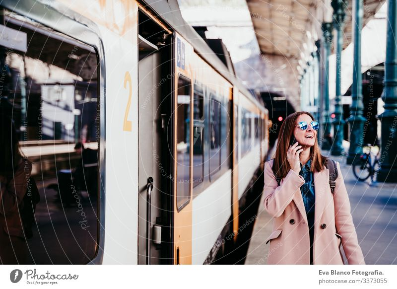 junge Frau am Bahnhof, die ein Mobiltelefon benutzt. Reisekonzept Bildschirm Ausflugsziel reisen Rucksack Kaukasier Europa Eisenbahn Warten Wagen Schiene
