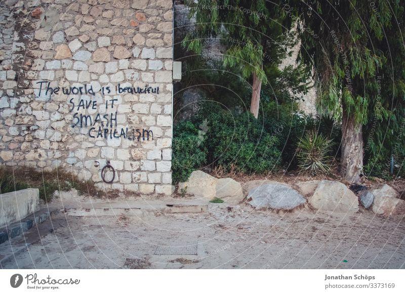 Mauer mit Schriftzug: Die Welt ist wunderschön, rette sie, zerstöre Kapitalismus Tag Menschenleer Außenaufnahme Farbfoto Wirtschaftskrise nachhaltig