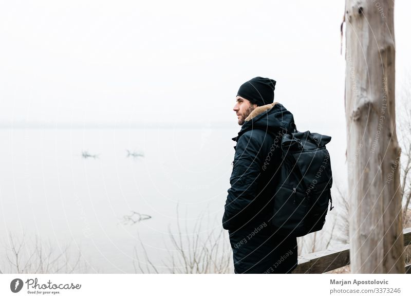 Junger Mann steht am Wintermorgen am Fluss aktiv Aktivität Erwachsener Abenteuer allein Rucksack lässig Küste kalt Landschaft Tag genießen Entdecker neblig