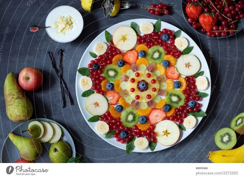 gemischter Obstsalat als Muster auf weißem Teller angeordnet Lebensmittel Frucht Apfel Vanilleschote Birne Kiwi Zitrone Weintrauben Zitronenmelisse Sahne