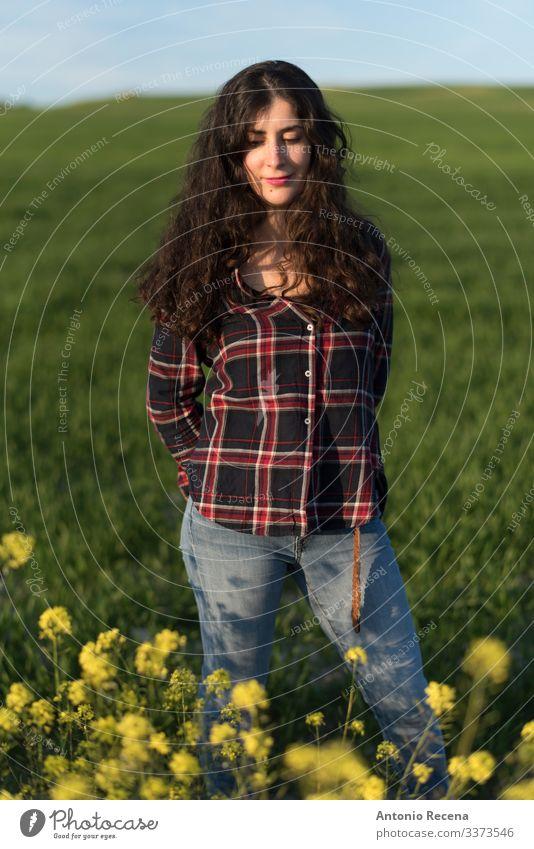 Hübsche Frau im Frühlingsporträt Lifestyle Mensch Erwachsene Blume Wiese Hemd Jeanshose langhaarig stehen Spanisch Sonnenuntergang kariertes Hemd Menschen