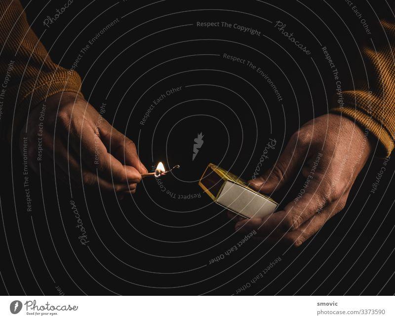 Die Hände eines erwachsenen Mannes, der ein brennendes Streichholz hält Mensch maskulin Erwachsene Leben Hand 1 30-45 Jahre Feuer Kasten Holz Rauch Armut Senior
