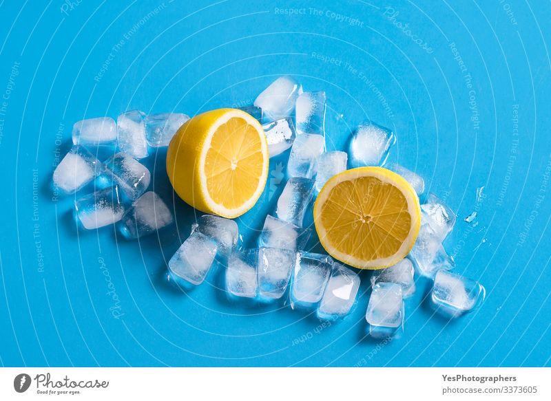Frische Zitrone, in zwei Hälften geschnitten, auf Eiswürfeln. Zitrusfrüchte Frucht Erfrischungsgetränk Gesunde Ernährung Blauer Hintergrund farbenfroh