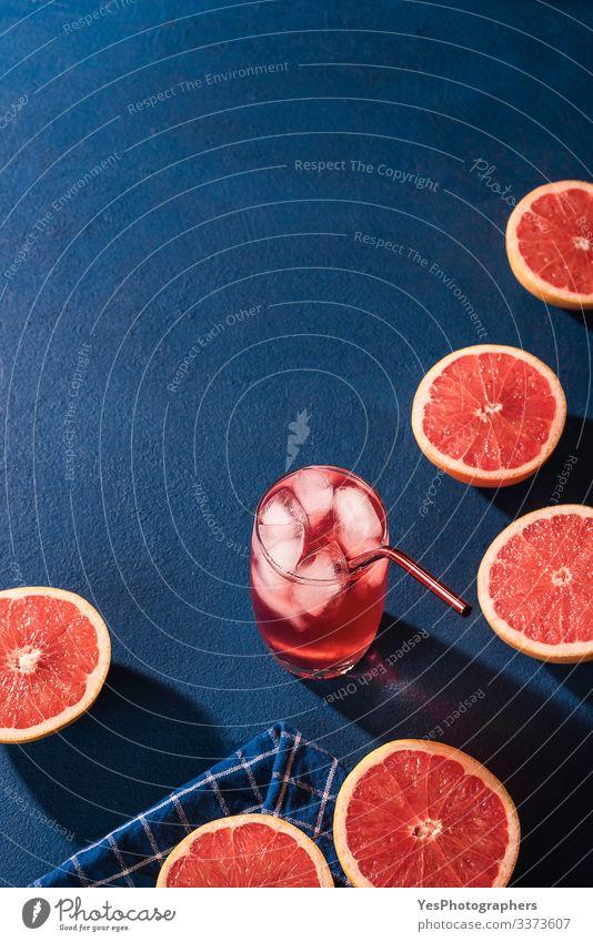 Bio-Grapefruitscheiben und Kaltgetränk. Limonade Frucht Getränk Erfrischungsgetränk Saft Glas saftig Farbe Blauer Hintergrund blauer Tisch Zitrusfrüchte