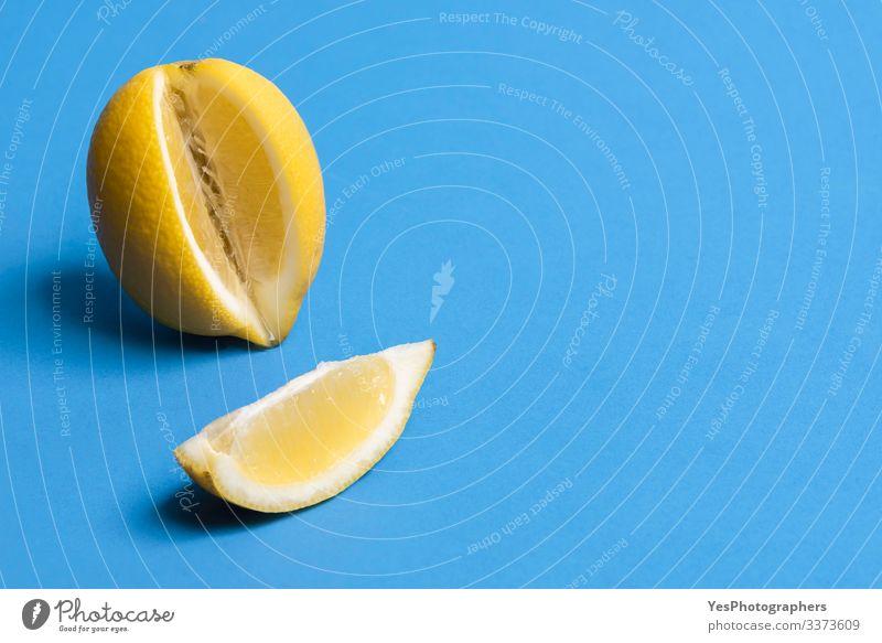 Reife Zitrone und eine Zitronenscheibe. Zitrusfrüchte. Frisches Obst Frucht Gesunde Ernährung frisch Blauer Hintergrund farbenfroh Textfreiraum Lebensmittel