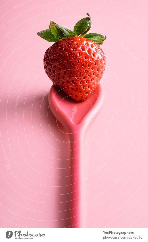 Eine einzelne Erdbeere auf einem Löffel. Reife Erdbeere auf rosa Lebensmittel Frucht Dessert Bioprodukte frisch farbenfroh süße Frucht Diätnahrung frisches Obst