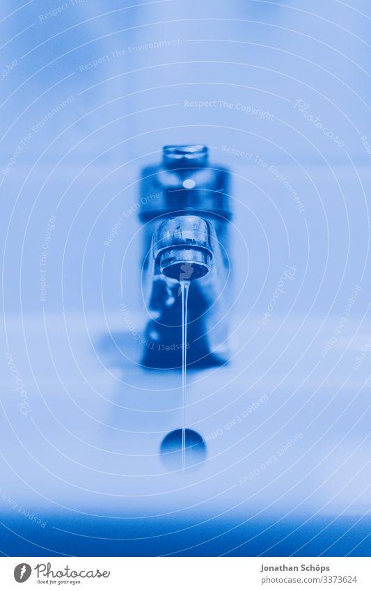 Wasserhahn mit ein wenig Wasser in einem Badezimmer in Blautönen Blauton Handhygiene Hygiene Gesundheit blau Nahaufnahme Innenbereich Sauberkeit Metall nass
